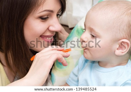 Young mother feeding baby boy - stock photo