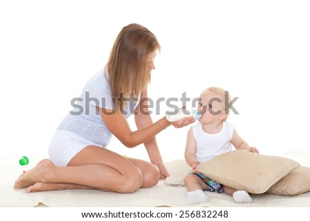 Young mother feeding baby from bottle on a white background. Happy family. - stock photo