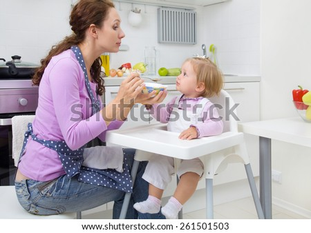young mother feeding baby with a spoon in the kitchen at home