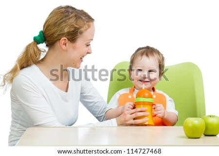 young mother feeding her baby boy isolated on white - stock photo
