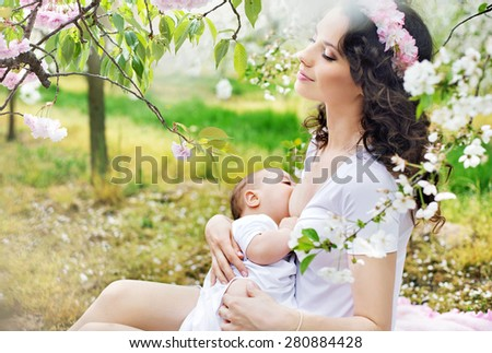 Young mother feeding her little baby in a spring orchard - stock photo