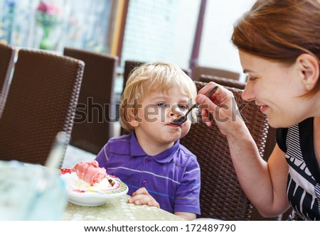 Young mother feeding her little boy son with ice-cream in city cafe in summer. - stock photo