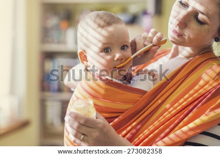 Young mother feeding her little daughter that she has in a baby carrier - stock photo