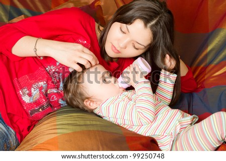young mother feeds child girl with a bottle with infant formula on bad - stock photo