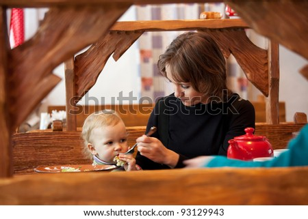 Young mother feeds her daughter in a cafe - stock photo