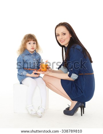 Young mother feeds  her daughter on a white background. Happy family. - stock photo
