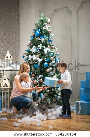 Young mother giving a present to the oldest son, baby boy touching bauble on Christmas tree - stock photo