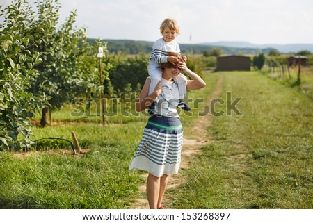 Young mother giving little boy a ride on shoulders on countryside in Germany