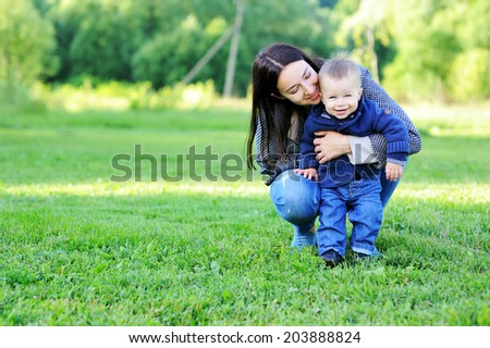 Young mother has fun with her baby boy on the green lawn in the park  - stock photo