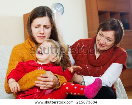 Young mother has problems. Mature woman comforting adult daughter with crying baby in living room at home - stock photo