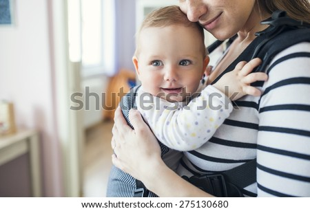 Young mother having her cute little daughter in baby carrier - stock photo