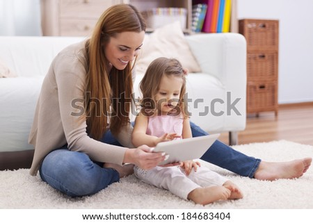 Young mother helping her daughter with digital tablet  - stock photo