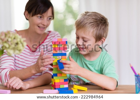 Young mother helping her small son build a tower from colorful building blocks as they sit together at the dining table at home - stock photo