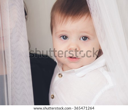 Young mother holding a baby standing in a tulle - stock photo