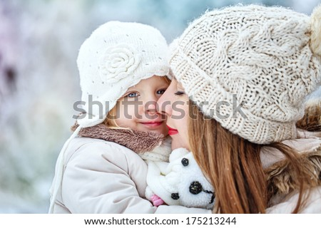 Young mother holding a daughter in a winter forest for a walk - stock photo