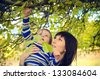Young mother holding a pretty little boy in nature under the trees - stock photo
