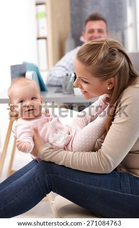 Young mother holding baby daughter on lap, playing with her, having fun.