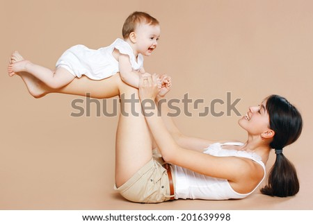 Young mother holding baby, fun, exercise, leisure - concept - stock photo