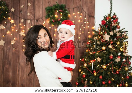 Young mother holding baby in santa suit indoor with Xmas tree - stock photo