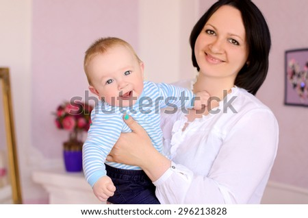 young mother holding cheerful smiling baby son indoors - stock photo