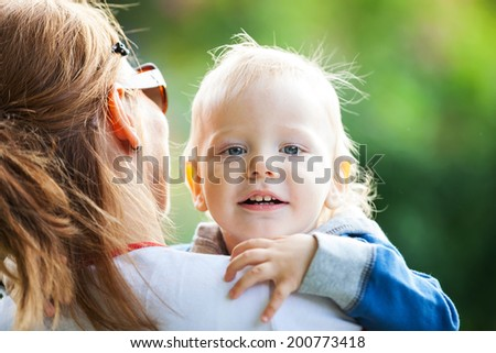 Young mother holding happy toddler boy  - stock photo
