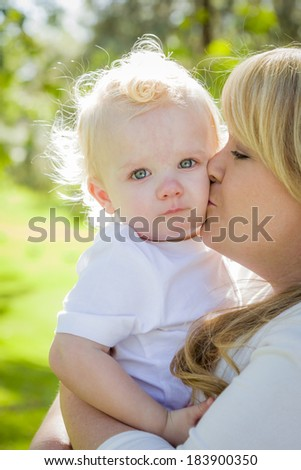 Young Mother Holding Her Adorable Baby Boy in the Park. - stock photo