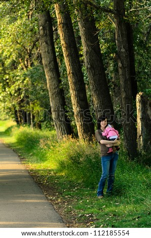Young mother holding her baby daughter in an outdoor park. - stock photo