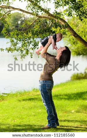 Young mother holding her baby daughter in an outdoor park by a river.