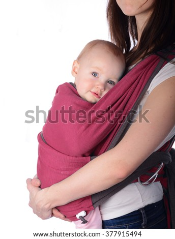 Young mother holding her cute daughter in baby carrier - stock photo