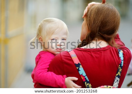 Young mother holding her cute toddler girl on a summer day outdoors