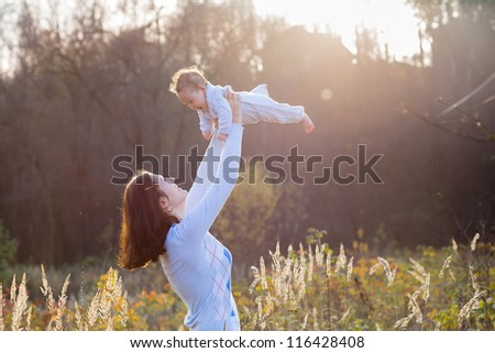 Young mother holding her little baby on a sunny day in a meadow - stock photo