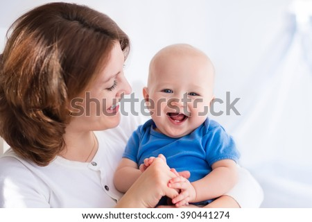 Young mother holding her newborn child. Mom nursing baby. Woman and new born boy in white bedroom with rocking chair and blue crib. Nursery interior. Mother playing with laughing kid. Family at home - stock photo