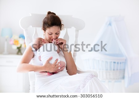 Young mother holding her newborn child. Mom nursing baby. Woman and new born boy relax in a white bedroom with rocking chair and blue crib. Nursery interior. Mother breast feeding baby. Family at home - stock photo