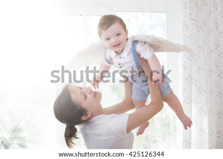 Young mother holding her newborn child. Mom nursing baby. Woman and new born boy relax in a white bedroom. Nursery interior. Mother breast feeding baby. Family at home - stock photo