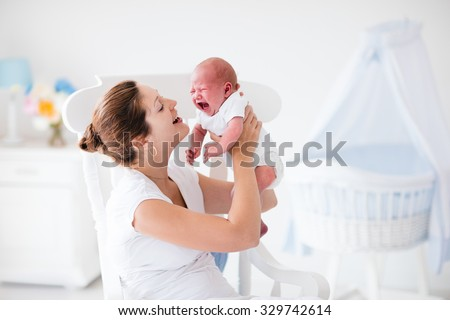 Young mother holding her newborn child. Mother comforting crying hungry baby. Woman and new born boy relax in a white bedroom with rocking chair and blue crib. Nursery interior. Family at home. - stock photo