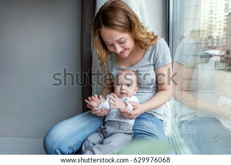 Young mother holding her newborn child. Woman and new born boy relax in a white bedroom near the windiow. Mother breast feeding baby. Family at home. Young mother playing whith her newborn son