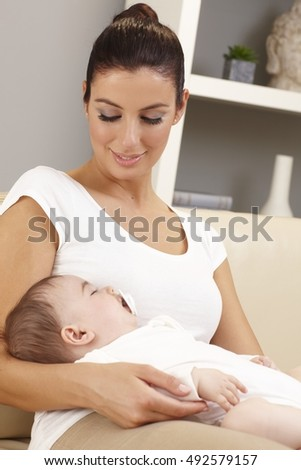Young mother holding sleeping baby in arms, looking affectionate.