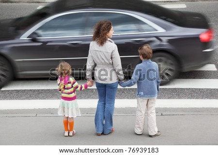 young mother holds hand of his little daughter and son and standing near cross road, behind, black car - stock photo