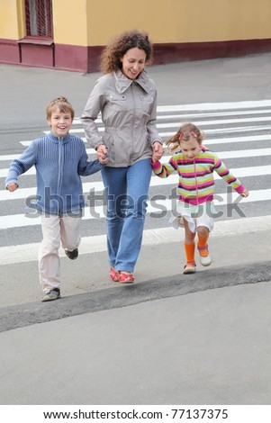 young mother holds hand of little daughter and son and crossing road, yellow house, focus on boy - stock photo