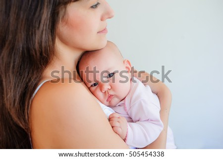 Young mother holds the child near a breast. Mother and daughter