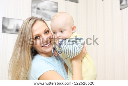 Young mother hugging baby  at home - stock photo