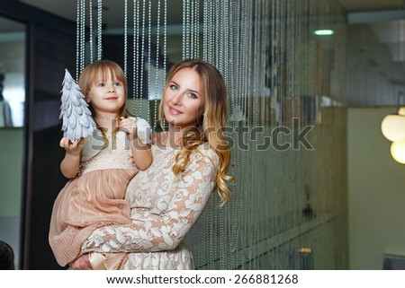 Young mother hugging her daughter tenderly. Mother holds daughter on hands. Daughter holds the mock of the Christmas tree. The concept of family happiness. - stock photo