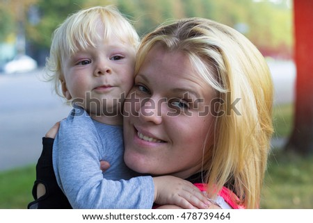 Young mother hugging her son on walk