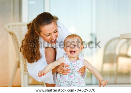 Young mother in bathrobe playing with baby on terrace