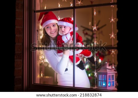 Young mother in red Christmas hat and her baby boy dressed in Santa costume standing next to a window in a decorated living room celebrating Xmas with lights and tree. View from outside of the house. - stock photo