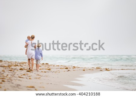 Young mother in white dress walking with her two little boy along the ocean beach. Woman with a baby and a boy enjoying vacation by the sea. On the empty beach. Motherhood. - stock photo
