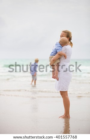 Young mother in white dress walking with her two little boys along the ocean beach. Woman with children enjoying vacation by the sea. Motherhood. Beautiful family. Water background. copy space.