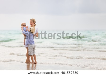 Young mother in white dress walking with her two little boys along the ocean beach. Woman with children enjoying vacation by the sea. Motherhood. Beautiful family. Water background. copy space. - stock photo