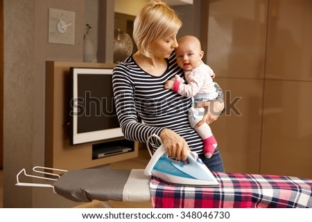 Young mother ironing while holding baby in arm.