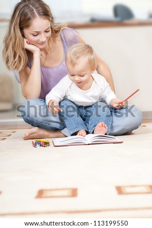 Young mother is drawing with her son - stock photo
